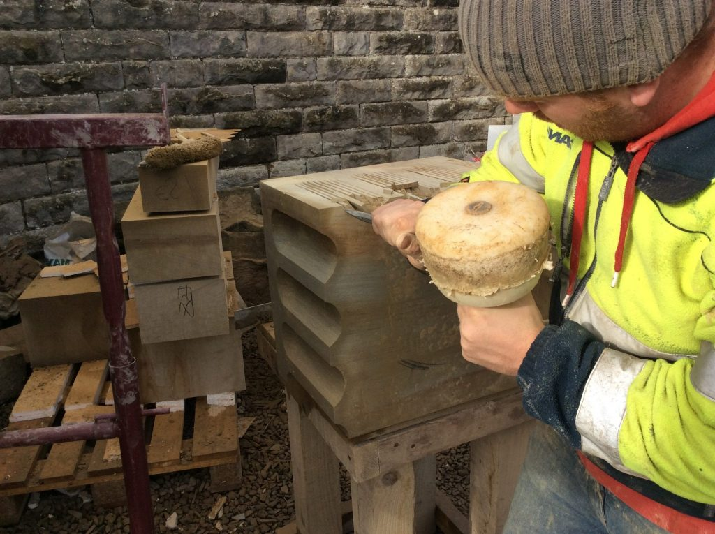 A stonemason carving a piece of stone on a historic building